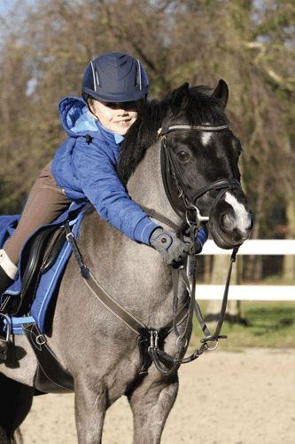 garçon heureux sur son poney noir, équitation pour les enfants