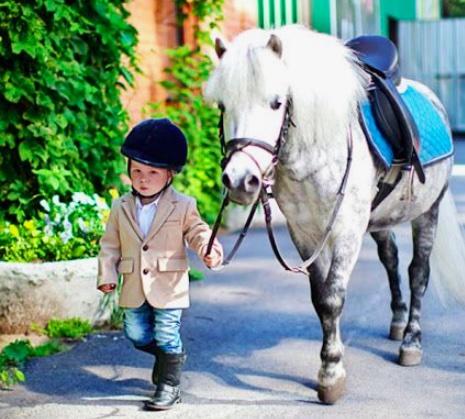 petit garçon de 4 ans en tenue du cheval avec un poney gris. quel sport faire faire à son enfant ?